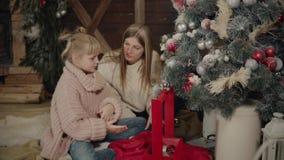 Glad jul och lyckligt nytt år Mamman och dottern dekorerar julgranen inomhus Älska upp familjslut arkivfilmer