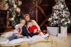 Glad jul och lyckligt nytt år Momand barn som har gyckel nära julgranen inomhus nära julgranen arkivfoto