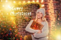 Glad jul och lyckligt nytt år! Stående av den lyckliga gladlynta härliga kvinnan i stucken hatttröja Arkivbild