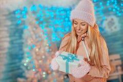 Glad jul och lyckligt nytt år! Ståenden av den lyckliga gladlynta härliga kvinnan i stack hatttumvanten som rymmer feriegåva, box royaltyfri fotografi