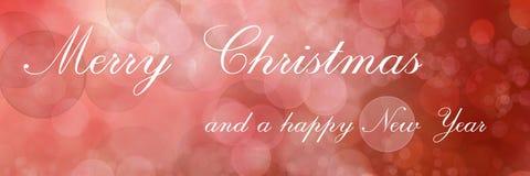 Glad jul och lyckligt nytt ett år som märker på röd suddig bakgrund royaltyfria foton