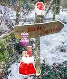 Glad jul på en riktningsteckenstolpe som dekoreras med jul för en Santa Claus hatt, klumpa ihop sig och en påse med gåvor bredvid arkivfoto