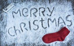 Glad jul räcker utdragen bokstäver med den röda sockan på träboa Arkivfoton