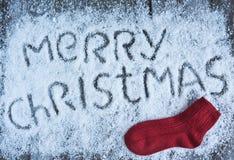 Glad jul räcker utdragen bokstäver med den röda sockan på träboa Arkivfoto