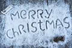 Glad jul räcker utdragen bokstäver med sörjer kottar på träb Royaltyfria Bilder