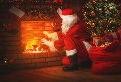 Glad jul! Santa Claus nära spisen och trädet med gi arkivfoto