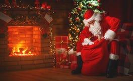 Glad jul! Santa Claus nära spisen och trädet med gi royaltyfri foto