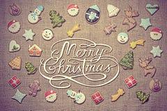 Glad jul! skriftligt bland dekorativa pepparkakakakor Tillfogad tappningblick Royaltyfri Foto