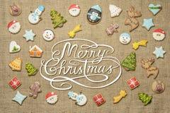 Glad jul! skriftligt bland pepparkakakakor Arkivfoto