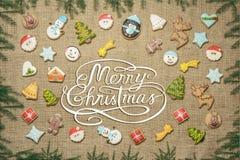 Glad jul! skriftligt bland pepparkakakakor som omges med gran, förgrena sig Royaltyfri Fotografi