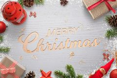 Glad jul smsar snidit i en träyttersida och omgivet av julpynt Arkivbilder