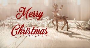 Glad jul smsar tecknet på renprydnader med hälsningkortet och på lantlig träbakgrund Säsongsbetonat hälsningsbegrepp arkivfoto
