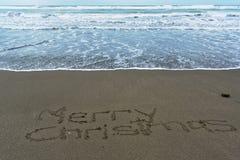 Glad jul som är skriftlig i sanden med tidvattnet som in kommer royaltyfria bilder