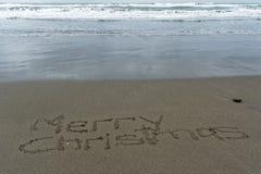 Glad jul som är skriftlig i sanden med våt sand bakom fotografering för bildbyråer