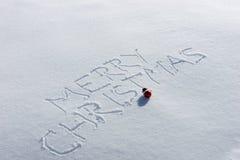 Glad jul som är skriftlig i snön Arkivfoto