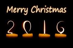 Glad jul 2016 som är skriftlig med stearinljusflammor arkivbilder