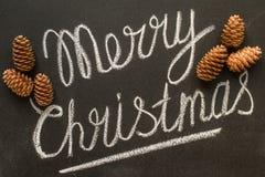 Glad jul som är skriftlig på ett lyckligt nytt år för svart tavlabegrepp Arkivfoton