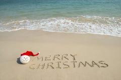 Glad jul som är skriftlig på vit sand för tropisk strand med snögubben royaltyfri foto