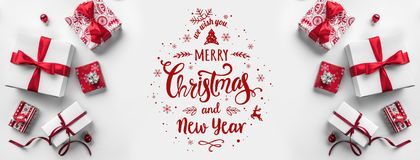 Glad jul som är typografisk på vit bakgrund med gåvaaskar och röd garnering royaltyfri bild