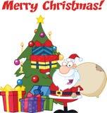 Glad jul som hälsar med Santa Claus Holding Up per bunt av gåvor vid en julgran Arkivbild