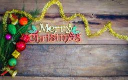 Glad jul som hälsar meddelandet på träbakgrund Arkivbild
