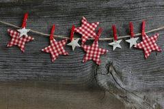 Glad jul som hänger garneringgingham- och björkstjärnor med Royaltyfria Foton