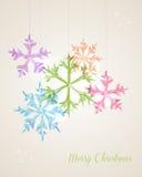 Glad jul som hänger snöflingahälsningkortet Royaltyfri Fotografi