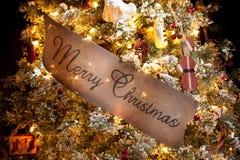 Glad jul undertecknar in en julgran Arkivfoton