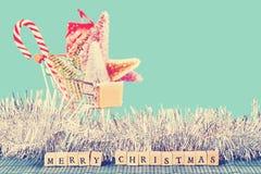 Glad jul undertecknar med shoppingvagnen i bakgrund Fotografering för Bildbyråer