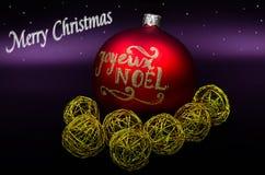 Glad jul undertecknar och guld- bollar som är röda och Arkivbilder