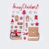 Glad julkort med textbokstäver, feriegåvan, hantverkpapper, bandet, tappningleksaker, etiketter, kakor och pepparkakan på vit royaltyfria foton