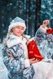 Glad jungfru i festlig dräkt lilla flickan är le och rymma nytt års leksak och påse med gåvor glad vinterskog royaltyfria foton