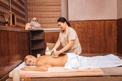 Glad kompetent massös som gör massage med speciala påsar royaltyfria bilder