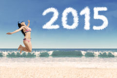 Glad kvinna i bikini med nummer 2015 Royaltyfria Bilder