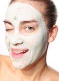 Glad kvinna i maskeringen med grön lera Arkivbild