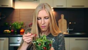 Glad kvinna som äter sund sallad Härlig ung kvinnlig som tycker om sund grönsaksallad och ser kameran medan lager videofilmer
