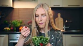 Glad kvinna som äter sund sallad Härlig ung kvinnlig som tycker om sund grönsaksallad och ser kameran medan arkivfilmer