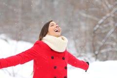 Glad kvinna som andas ny luft som tycker om snö arkivfoto