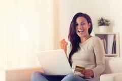Glad kvinna som använder bärbara datorn och direktanslutet köper med kreditkorten royaltyfri bild
