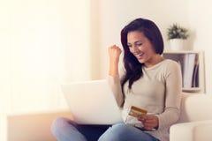 Glad kvinna som använder bärbara datorn och direktanslutet köper med kreditkorten royaltyfria foton