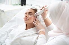Glad kvinna som får behandling av hud arkivfoto