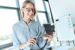 Glad kvinna som gör en appell på en landlinekontorstelefon Royaltyfria Bilder