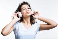 Glad kvinna som lyssnar till favorit- sånger och att le royaltyfri fotografi