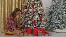 Glad kvinna som ordnar gåvor under julträd stock video