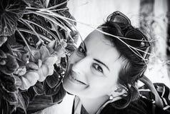 Glad kvinna som poserar med blommor, Telc som är akromatisk Royaltyfria Bilder