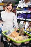 Glad kvinna som talar på telefonen om shopping Royaltyfri Fotografi