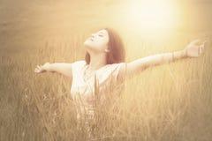 Glad kvinna som tycker om ny luft på äng Arkivbilder