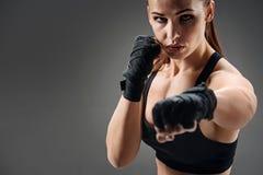 Glad kvinnaboxning på en grå bakgrund royaltyfria bilder