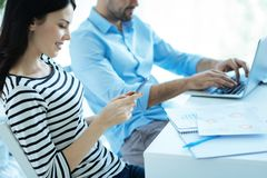 Glad kvinnlig anställd som använder smartphonen på arbete Arkivfoton