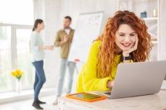 Glad kvinnlig anställd som arbetar med bärbara datorn fotografering för bildbyråer